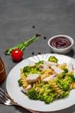 Pâtes de Fusilli avec du blanc de poulet et la salade de brocoli dans le plat blanc image stock