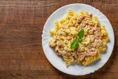 Pâtes de Fusilli avec de la sauce et le fromage à Carbonara dans le plat blanc sur la table en bois photos libres de droits