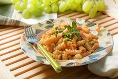 Pâtes de Fusilli avec la sauce tomate et les pois Photographie stock