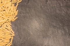 Pâtes de macaronis de Penne Rigate sur la surface de fonctionnement grise Photographie stock