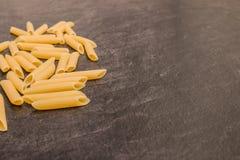 Pâtes de macaronis de Penne Rigate sur la surface de fonctionnement grise Photo libre de droits