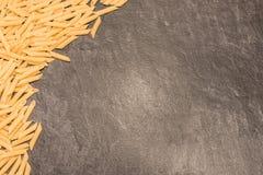 Pâtes de macaronis de Penne Rigate sur la surface de fonctionnement grise Image libre de droits