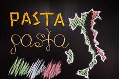 Pâtes de mots faites de spaghetti cuits et pâtes sèches sur le fond noir avec le cadre du pays Italie écrit par la craie Photos stock