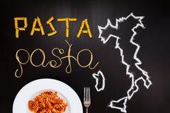 Pâtes de mots faites de spaghetti cuits et pâtes sèches sur le fond noir avec le cadre du pays Italie écrit par la craie Photo stock