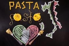 Pâtes de mots faites de spaghetti cuits et pâtes sèches sur le fond noir avec le cadre du pays Italie et du coeur Photos libres de droits