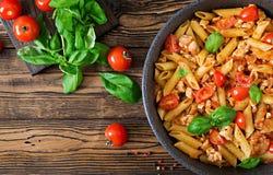 Pâtes de Penne en sauce tomate avec le poulet, tomates, décorées du basilic Image stock