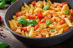 Pâtes de Penne en sauce tomate avec le poulet, tomates, décorées du basilic Photographie stock