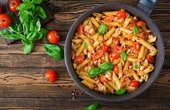 Pâtes de Penne en sauce tomate avec le poulet, tomates, décorées du basilic Photos stock