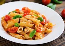 Pâtes de Penne en sauce tomate avec le poulet, tomates, décorées du basilic Photo libre de droits