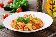 Pâtes de Penne en sauce tomate avec le poulet, tomates, décorées du basilic Image libre de droits