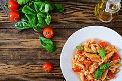 Pâtes de Penne en sauce tomate avec le poulet, tomates, décorées du basilic Photo stock