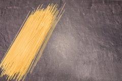 Pâtes de spaghetti sur la surface de fonctionnement grise Images libres de droits