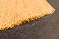 Pâtes de spaghetti sur la surface de fonctionnement grise Photographie stock libre de droits