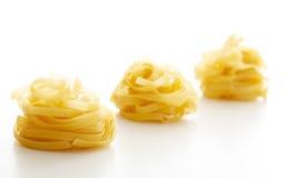 Pâtes de Tagliatelle sur le fond blanc Image stock