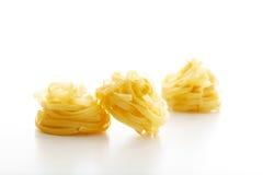 Pâtes de Tagliatelle sur le fond blanc Images stock