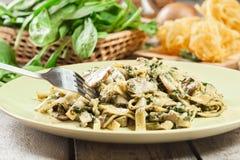 Pâtes de tagliatelles avec des épinards et des champignons d'un plat Photos stock