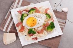 Pâtes de tagliatelles avec le brocoli, le prosciutto et l'oeuf au plat Photographie stock