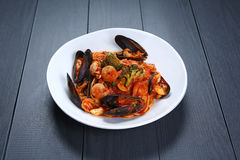 Pâtes de tomate de fruits de mer avec la crevette et les palourdes du plat blanc images libres de droits