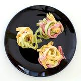 Pâtes de trois couleurs sur le plat noir prêt à servi Image stock