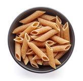 Pâtes entières de grain dans la cuvette d'isolement sur le blanc, d'en haut images stock