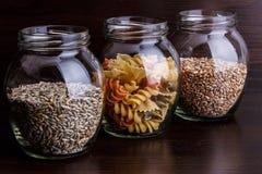 Pâtes et grains de blé sec dans un pot sur le macro en bois foncé de plan rapproché de fond Photo stock