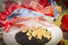 Pâtes et lentilles noires de beluga et une pile des rubans de cadeau Photos stock
