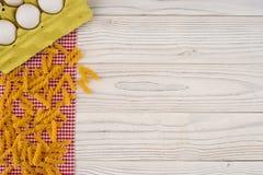 Pâtes et oeufs dans un plateau sur une vieille table en bois blanche Image libre de droits