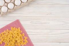 Pâtes et oeufs dans un plateau sur une vieille table en bois blanche Photo libre de droits