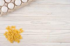 Pâtes et oeufs dans un plateau sur une vieille table en bois blanche Photos stock