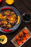 Pâtes et poivre d'un plat gris avec des tomates, poivron doux, citron, olives sur un fond foncé en bois Ingrédients pour Image stock