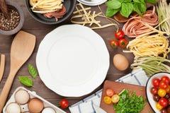 Pâtes faisant cuire des ingrédients et des ustensiles sur la table en bois Photo libre de droits