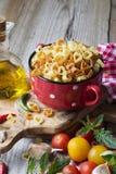 Pâtes faites maison Italien traditionnel sous forme de coeurs dans un pot en céramique rouge avant la cuisson Photo stock