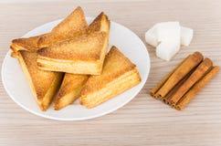 Pâtes feuilletées dans le plat, morceaux de sucre grumeleux et cannelle Images stock