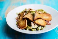 Pâtes fraîches avec le lard et les champignons d'huîtres de roi images stock