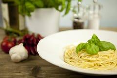 Pâtes fraîches savoureuses avec l'ail et basilic sur la table images stock