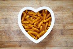 Pâtes gratuites de gluten dans la cuvette de forme de coeur Photos stock