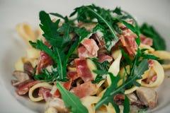 Pâtes italiennes avec le plan rapproché d'arugula et de jambon Image stock