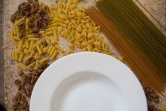 Pâtes italiennes crues avec un plat blanc image stock