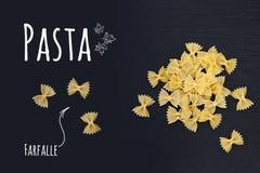 Pâtes italiennes crues Farfalle sur le fond noir de pierre d'ardoise Photo stock