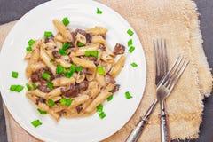 Pâtes italiennes délicieuses de penne avec les champignons crémeux frits champignon de paris, oignon, oignons blancs coupés chevr photos stock