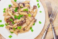 Pâtes italiennes délicieuses de penne avec les champignons crémeux frits champignon de paris, oignon, oignons blancs coupés chevr images stock