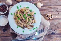Pâtes italiennes délicieuses de penne avec les champignons crémeux frits champignon de paris, oignon, oignons blancs coupés chevr photos libres de droits