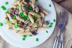 Pâtes italiennes délicieuses de penne avec les champignons crémeux frits champignon de paris, oignon, oignons blancs coupés chevr photo libre de droits