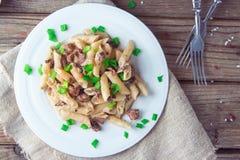 Pâtes italiennes délicieuses de penne avec les champignons crémeux frits champignon de paris, oignon, oignons blancs coupés chevr image libre de droits