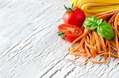 Pâtes italiennes rouges et blanches crues avec l'espace de copie de basilic Photos stock