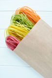 Pâtes multicolores crues dans un sac de papier Photos stock