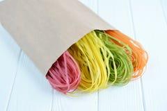 Pâtes multicolores crues dans un sac de papier Photo stock