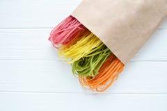 Pâtes multicolores crues dans un sac de papier Image stock