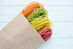Pâtes multicolores crues dans un sac de papier Image libre de droits