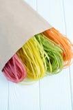 Pâtes multicolores crues dans un sac de papier Images stock